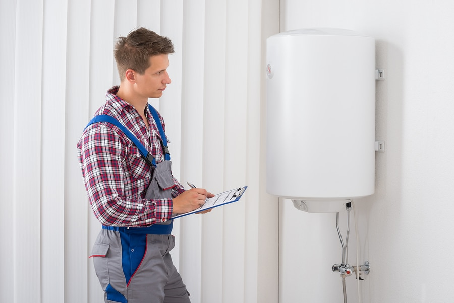 Young Male Plumber Holding Clipboard Checking Electric Boiler